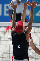 Two men beach volleyball players go up to the net trying to block the ball.
