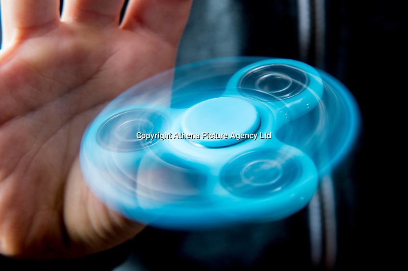 A young boy uses a bright blue fidget spinner