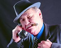 Photo shown of a man smoking a cigar, man, cigar, suit.