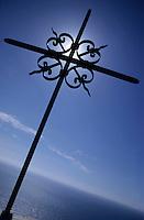 Wrought iron cross facing the sky above the Mediterranean Sea at Cape Corse, Nonza, Corsica, France.