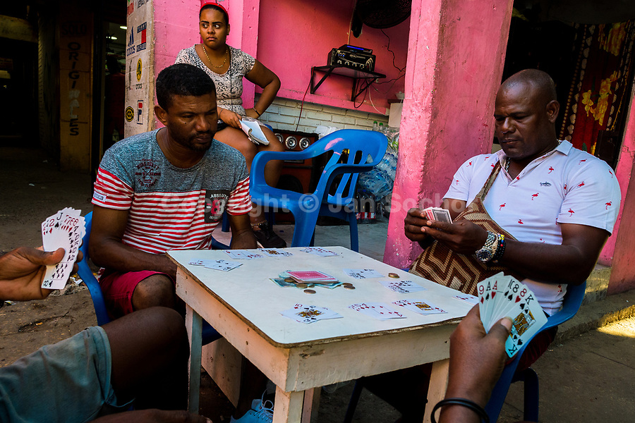 Afro-Colombian market vendors play cards at the end of the day in the market of Bazurto in Cartagena, Colombia, 5 December 2018. Far from the touristy places in the walled city, a colorful, vibrant labyrinth of Cartagena's biggest open-air market sprawls to the Caribbean seashore. Here, in the dark and narrow alleys, full of scrappy stalls selling fruit, vegetables and herbs, meat and raw fish, with smelly garbage on the floor and loud reggaeton music in the air, the African roots of Colombia are manifested.