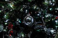 A silver ball Christmas ornament among lights and ornaments on a Christmas tree.