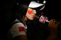 CHINA. Beijing. A woman drinking coca-cola in a stadium during the Beijing 2008 Summer Olympics. 2008