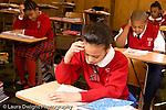 K-8 Parochial School Bronx New York Grade 4 children reading handout in class horizontal
