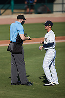 Charleston RiverDogs manager Blake Butera (3) gives home plate umpire Jacob McConnell a lineup change during the game against the Augusta GreenJackets at Joseph P. Riley, Jr. Park on June 27, 2021 in Charleston, South Carolina. (Brian Westerholt/Four Seam Images)