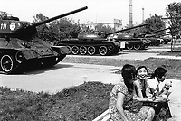 Kazakhstan. Semipalatinsk. A group of young teenagers girls sit on a bench at the Museum of Army. (L) T34 soviet tank from World War II and a row of other tanks from the former Soviet Union. Semey is the Kazakh name for Semipalatinsk and is located in the Eastern Kazakhstan Province. © 2008 Didier Ruef
