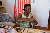 Haiti, Port-au-Prince, Haiti Design Coop a local artisan program run by Chandler Busby, mostly leather and jewelry products. People working in the workshop.