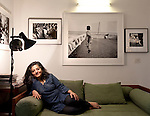 26 March 2013, Mumbai, INDIA:  Photographer Dayanita Singh relaxes under some of her photographs at her office in the New Delhi suburb of Vasant Vihar. Singh is preparing to participate in the Venice Biennial with a digital slideshow go her archive of photographs in the German Pavilion at Venice. PIcture by Graham Crouch