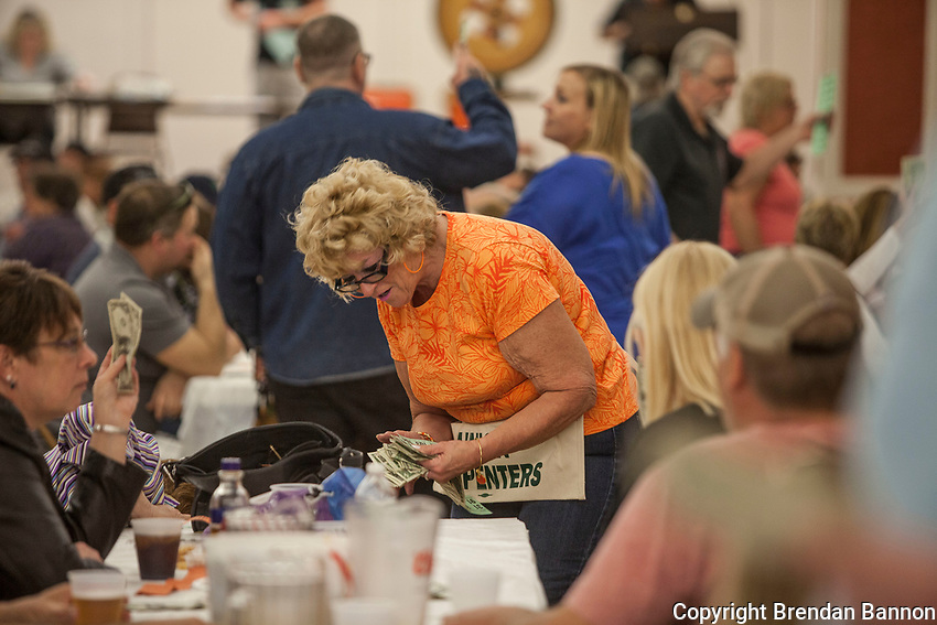 Collecting money for tickets at a meat raffle at the  Moose Lodge in Lancaster, NY.  Each spin of the wheel is for a specific pre-announced prize. Meat raffles have become poular fundraisers in Western New York. April 17, 2016