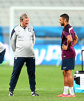 England manager Roy Hodgson talks to Alex Oxlade-Chamberlain, recovering from a knee injury, during training ahead of their Group D match vs Uruguay tomorrow