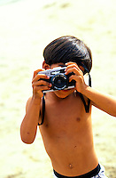 Little boy on vacation taking a picture on the beach- Big Island Hawaii