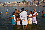 A priest helps offer a family their prayers to river Ganges in the ancient city of Varanasi in Uttar Pradesh, India. Photograph: Sanjit Das/Panos