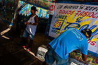 "Colombian sign painters work on a large music party poster in the sign painting workshop in Cartagena, Colombia, 14 April 2018. Hidden in the dark, narrow alleys of Bazurto market, a group of dozen young men gathered around José Corredor (""Runner""), the master painter, produce every day hundreds of hand-painted posters. Although the vast majority of the production is designed for a cheap visual promotion of popular Champeta music parties, held every weekend around the city, Runner and his apprentices also create other graphic design artworks, based on brush lettering technique. Using simple brushes and bright paints, the artisanal workshop keeps the traditional sign painting art alive."