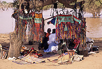 Akadaney, Central Niger, West Africa.  Tuareg Camel Bags, Decorative Leather Work, Hanging on Acacia Trees as Fulani Men Chat at Mid-Day, Annual Fulani Gathering, Geerewol.