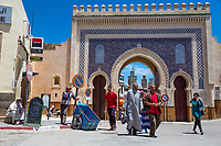 Fes, Morocco.  Bab Boujeloud, Entrance to Fes El-Bali, the Old City.  Men display two clothing styles: traditional djellaba and European-western style.