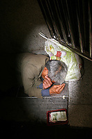 CHINA. Beijing. A homeless man sleeping in Xidan subway station . 2008