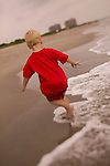 boy exploring the beach with waves hitting his feet