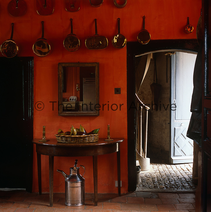 The walls of the kitchen have been painted a burnt orange and are decorated with copper saucepans original to the chateau