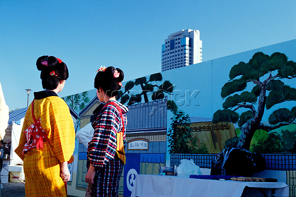 Two geishas dressed in kimonos in front of modern building