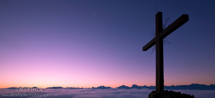 Dawn from the Schonjochl (2493 metres), with silhouette of cross in foreground. Nordtirol, Tirol, Austian Alps, Austria.