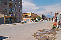 The street in front of the restaurant - typical Shkodra street with pot holed road, apartment buildings and signs 'lavazh' offering car wash. Tradita traditional restaurant, Shkodra. Albania, Balkan, Europe.