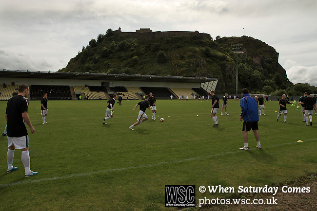 Dumbarton 0 Cowdenbeath 3, 18/08/2012. BetButler Stadium, Scottish League First Division. Home players taking part in their pre-match warm-up in the shadow of Dumbarton Rock at the BetButler Stadium before Dumbarton play Cowdenbeath in an Irn-Bru Scottish League First Division match. An original member of the league, Dumbarton, formed in 1872, moved from Boghead to their current home in 2001 and this was their first home game at the second tier of Scottish football since 1996. Cowdenbeath won the match by 3-0 watched by an attendance of 695. Photo by Colin McPherson.