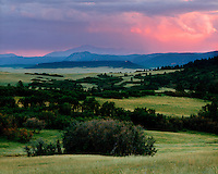 Sunset light on the hills of Greenland Ranch below Pikes Peak; Douglas County, CO