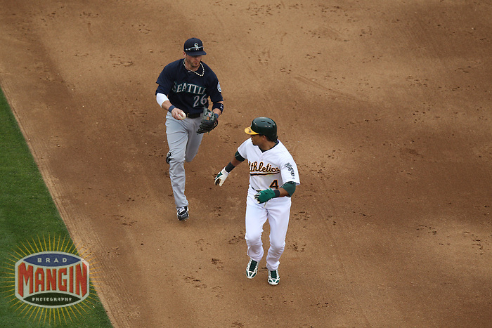 OAKLAND, CA - JUNE 15:  Brendan Ryan #26 of the Seattle Mariners chases Oakland Athletics base runner Coco Crisp #4 who is caught in the rundown between first and second base during the game at O.co Coliseum on Saturday June 15, 2013 in Oakland, California. Photo by Brad Mangin