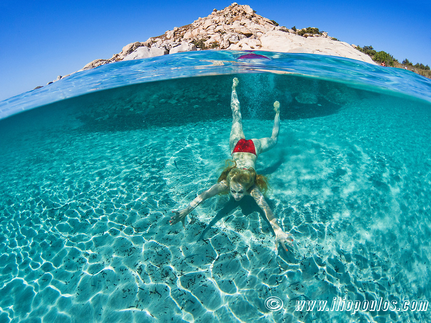Young woman swims at the bottom of an exotic beach on half underwater view