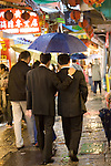 Two Asian men in suits share an umbrella while walking through the street market in Jioufen, Taipei County, Taiwan