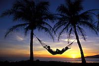 Couple enjoy a West Maui sunset in a hammock at Ka Puali, Maui.