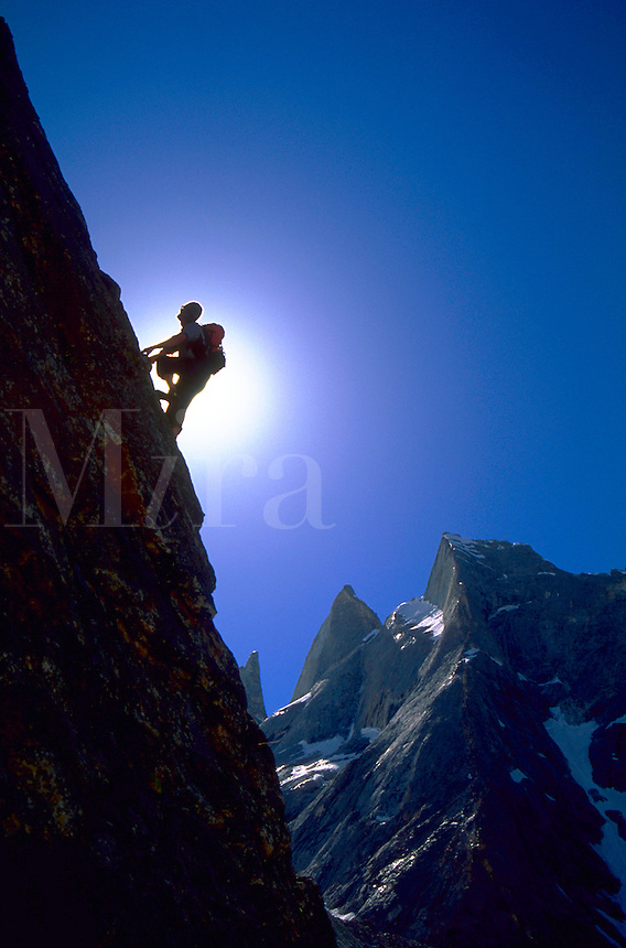 A climber on a steep rock face silhouetted against the sun and a blue sky in Charakusa Valley, Karakoram Himalaya, Pakistan.<br />