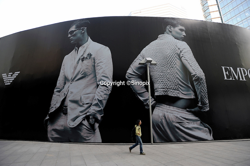 Chinese man walks past a huge billboard of Emporio Armani at Shin Kong Place, which is one of the most luxurious shopping centers in Beijing, having successfully attracted 938 international class brands, they also boast the largest Gucci flagship store in Asia..