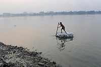A young boy pushes himself down the Ganges River in Kolkata.<br /> <br /> To license this image, please contact the National Geographic Creative Collection:<br /> <br /> Image ID: 1925855 <br />  <br /> Email: natgeocreative@ngs.org<br /> <br /> Telephone: 202 857 7537 / Toll Free 800 434 2244<br /> <br /> National Geographic Creative<br /> 1145 17th St NW, Washington DC 20036