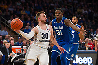 NEW YORK, NY - Thursday March 9, 2017: Andrew Rowsey (#30) of Marquette gets past Angel Delgado (#31) of Seton Hall as the two schools square off in the Quarterfinals of the Big East Tournament at Madison Square Garden.