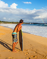 A skimboarder sees a rainbow from Big Beach, Makena State Park, Maui. (NOTE: The skimboarder is model released, the others in distance are not.)