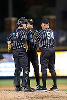 Charlotte Knights pitching coach Steve McCatty (54) has a meeting on the mound with relief pitcher Brad Goldberg (21) and catcher Kevan Smith (32) during the game against the Norfolk Tides at BB&T BallPark on May 2, 2017 in Charlotte, North Carolina.  The Knights defeated the Tides 8-3.  (Brian Westerholt/Four Seam Images)
