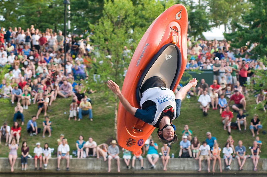 Flipping during the kayaking competition at Dominion River Rock this participant hopes to win. This event is held on the canal in Downtown Richmond, Virginia.