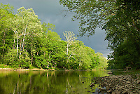 An ominous sky from an approaching storm contrasts sharply with the last rays of late-day sunlight draping the banks of Sugar Creek in Montgomery County, Indiana, USA. Mid-May. Sugar Creek is a popular canoeing destination that runs through two of Indiana's state parks--Shades State Park and Turkey Run State Park.