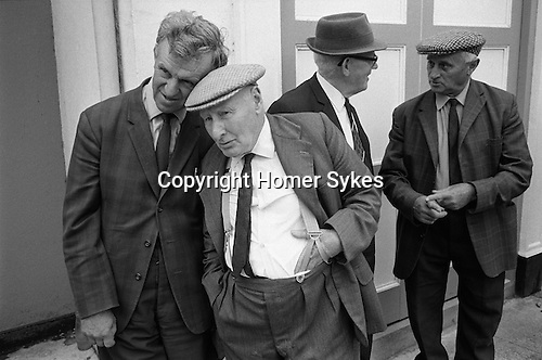 Men watching the Pretty Maid of Holsworthy  procession, Holsworthy, Devon England 1975