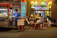 Street Food Vendor Tends Stand while Tourists Check their Cell Phones. Melaka, Malaysia.