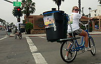 Vicky Bowman rides a bicycle equipped with a trash can at Garnet and Mission Blvd in Pacific Beach on the morning of July 5th, 2008.  Bowman along with Brie Cichy and Steve Kaelin (in background) were part of a group of volunteers who set out to collect trash from the beach after the big fourth of July holiday.  Volunteers and organisers of several beach clean-ups in the area were stunned by the lack of trash they found compared to what they are used to finding each year on July 5th after beachgoers leave.  The cleanliness of the beaches left many searching the side streets and alleys for trash to collect.  Most people are attributing the drastic change to the six-month old alcohol ban on the area beaches.