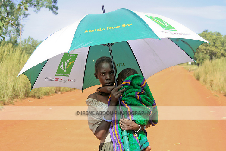 A girl holding a baby on the main road through Kotobi, South Sudan shades herself and the baby with an umbrella provided by Population Services International, a non-profit organization implementing an HIV/AIDS prevention project in Kotobi. Messages about how to prevent HIV/AIDS are printed on the umbrella...Kotobi is approximately 150 miles directly south of Rumbek (the former interim capital of South Sudan), on the main road from Rumbek to Uganda. .While this road is an important throughfare for traffic between Sudan and Uganda, the road is a dirt road, built by the United Nations World Food Programme. After generations of civil war, South Sudan has only a few kilometers of paved road.