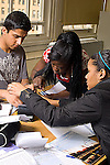 High school group of three students working on a science experiment on electricity