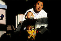 CHINA. Beijing. A young orphan and health worker in an orphanage outside of Beijing. 2007. There are currently millions of orphans in China living in orphanages spread throughout the country. As a result of China's one-child policy, many children are abandoned or given up if they suffer from any physical or mental handicap as the parents strive to have a child born 'normal' and well. This has led to may children being abandoned to live in state and privately-owned orphanages.