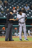 Augusta GreenJackets manager Jolbert Cabrera (8) gives a lineup change to home plate umpire Ben Fernandez during the game against the Greensboro Grasshoppers at First National Bank Field on April 10, 2018 in Greensboro, North Carolina.  The GreenJackets defeated the Grasshoppers 5-0.  (Brian Westerholt/Four Seam Images)
