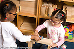 Preschool ages 3-5 two girls playing together in block area horizontal