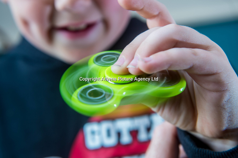 A young boy uses a fidget spinner