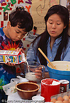 4 year old boy with mother at home baking stirring batter in bowl vertical