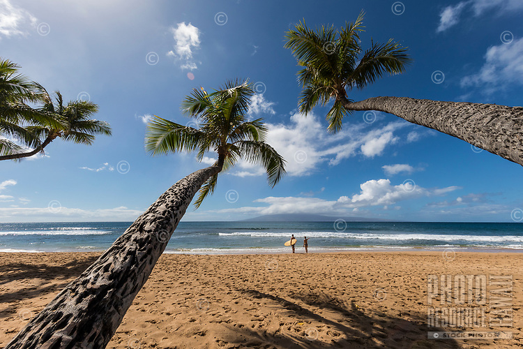 A man holding a surfboard and a woman enjoy a sunny day at Maui's Ka'anapali Beach, seen from a line of palm trees. The island of Lana'i can be seen in the distance.